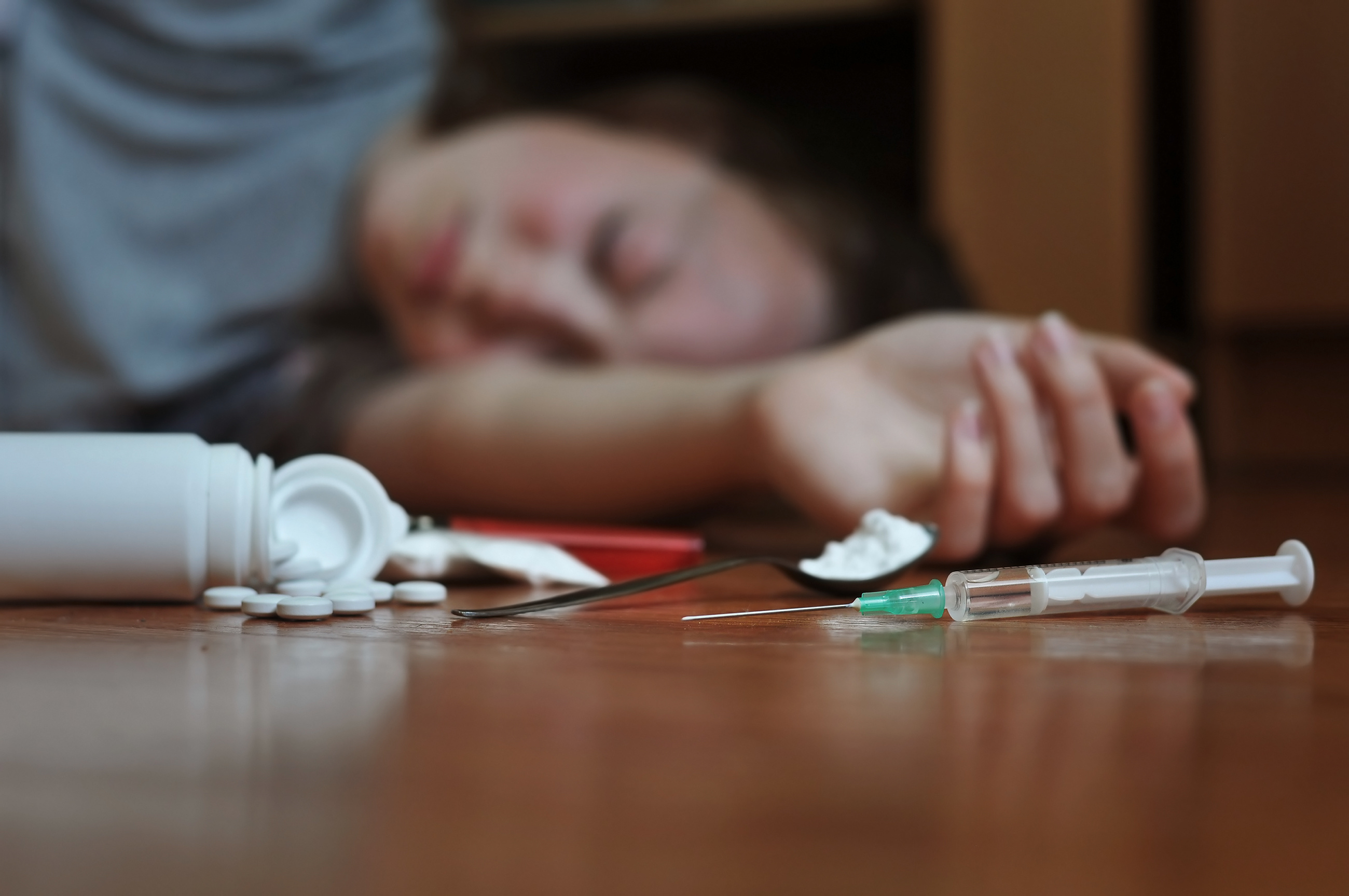drug addict on floor with drugs